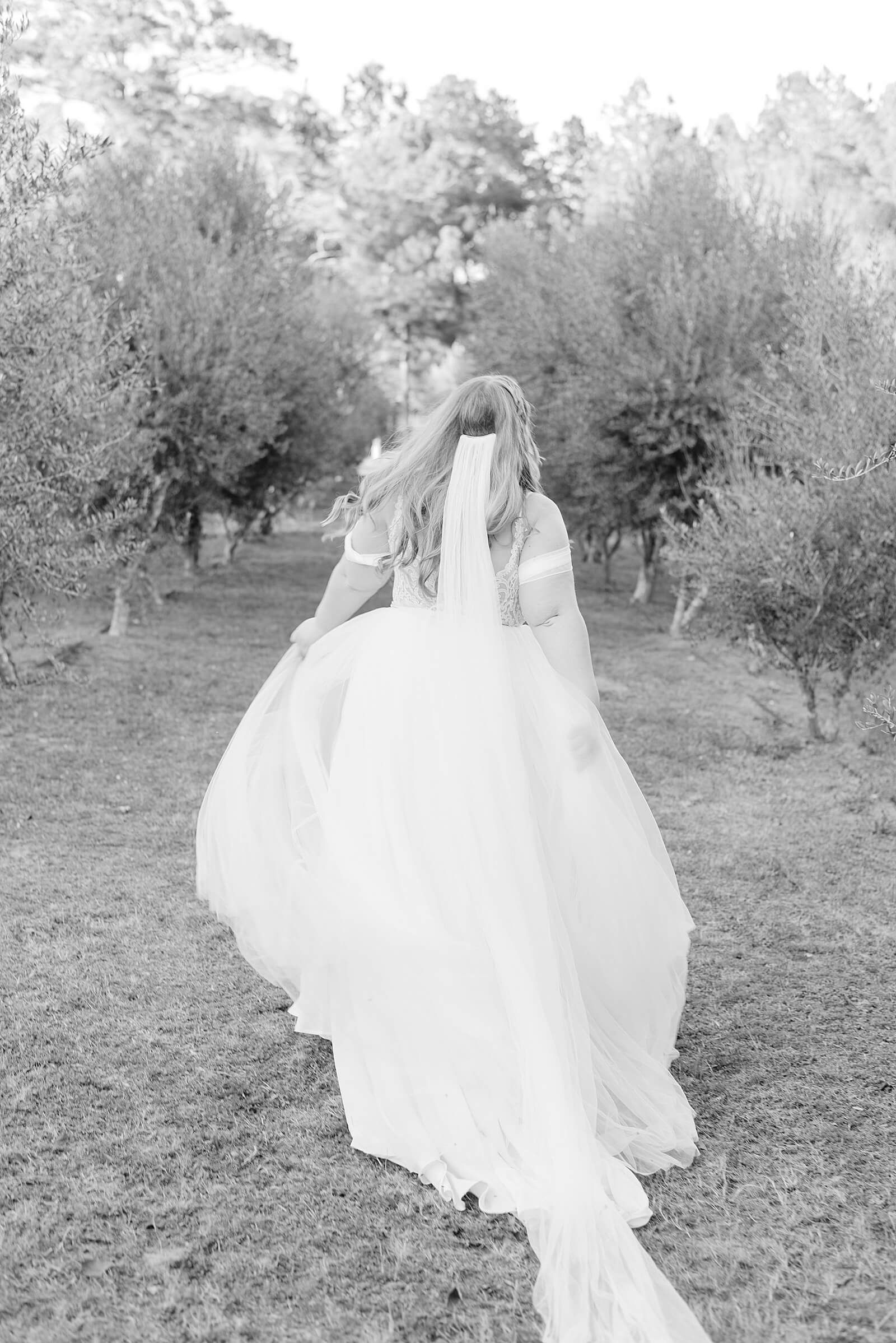 Happy bride running through olive trees at one of the elegant wedding venues in Houston
