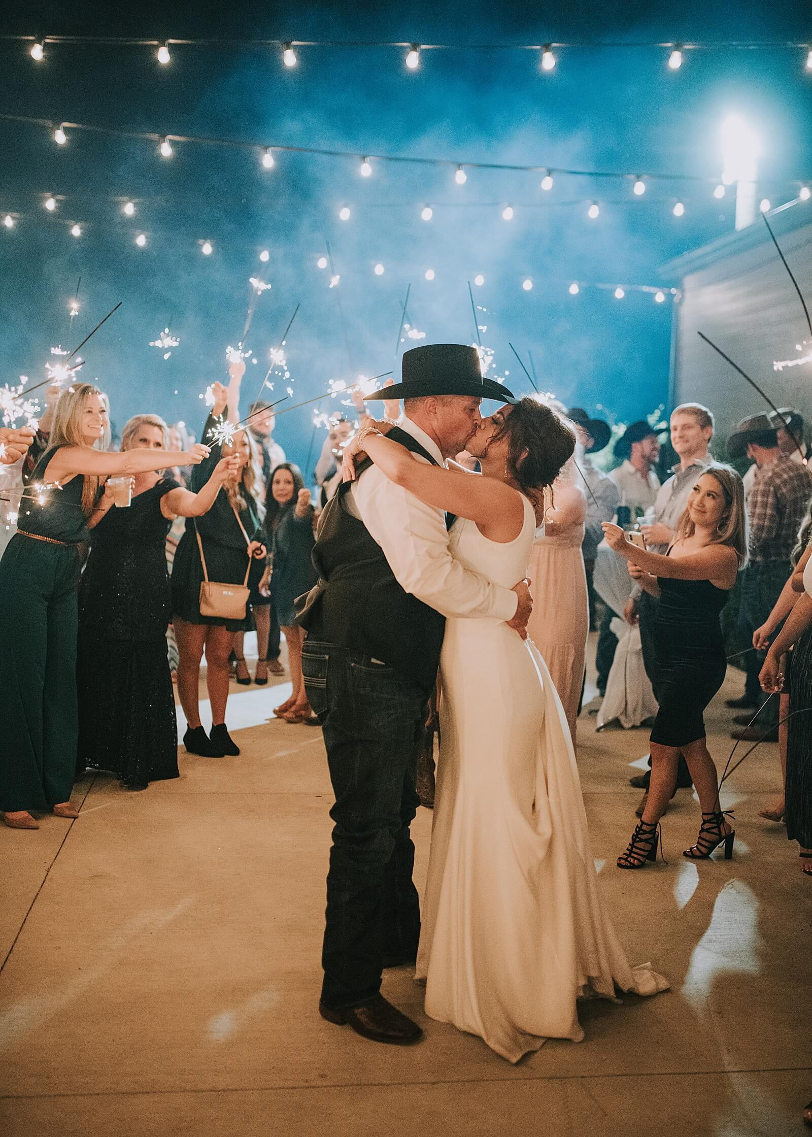 Couple shares kiss while surrounded by sparklers at The Annex Houston wedding venues