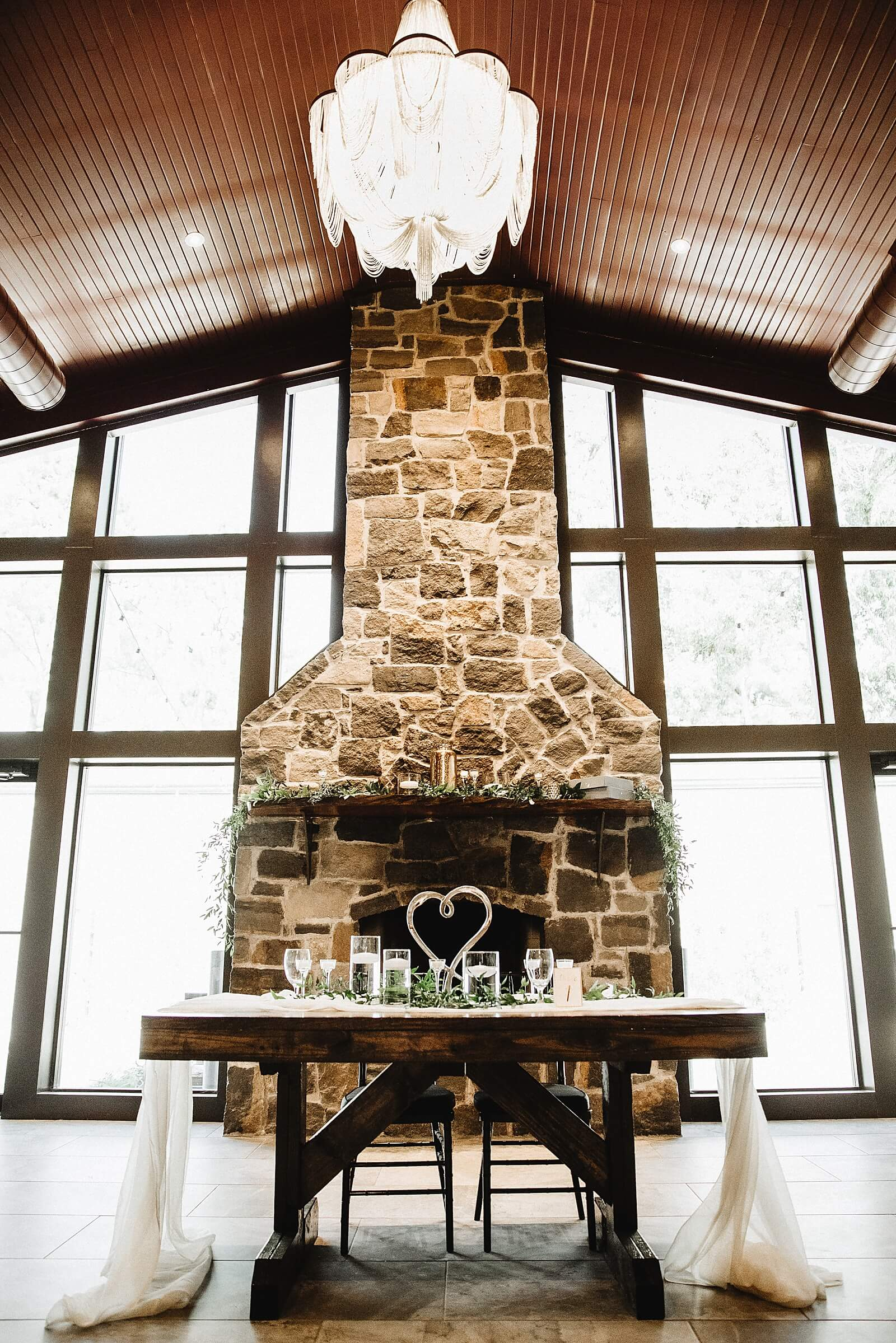 Sweetheart table in front of stone fireplace at one of the unique wedding venues in Houston The Annex