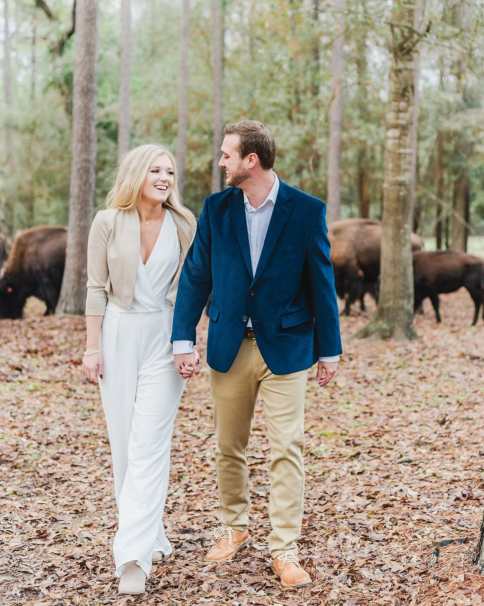 Engaged couple walks alongside buffalo at one of the unique wedding venues in Houston The Annex