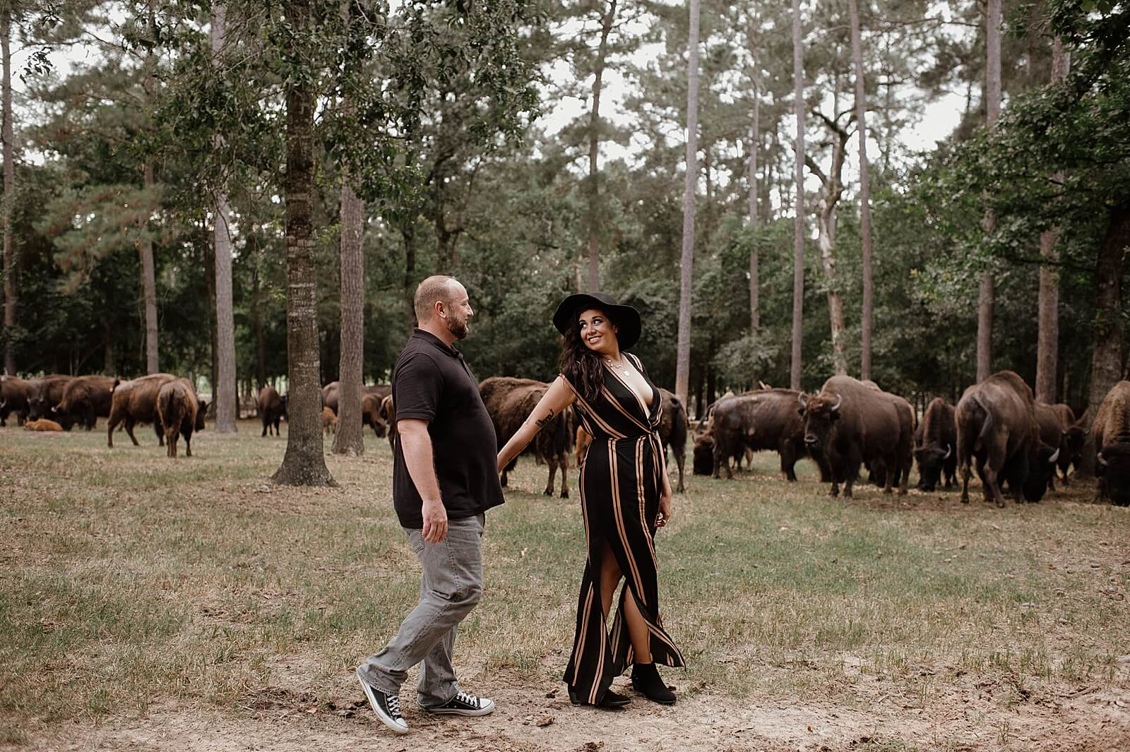 Couple walks in front of buffalo at one of the unique wedding venues in Houston The Annex