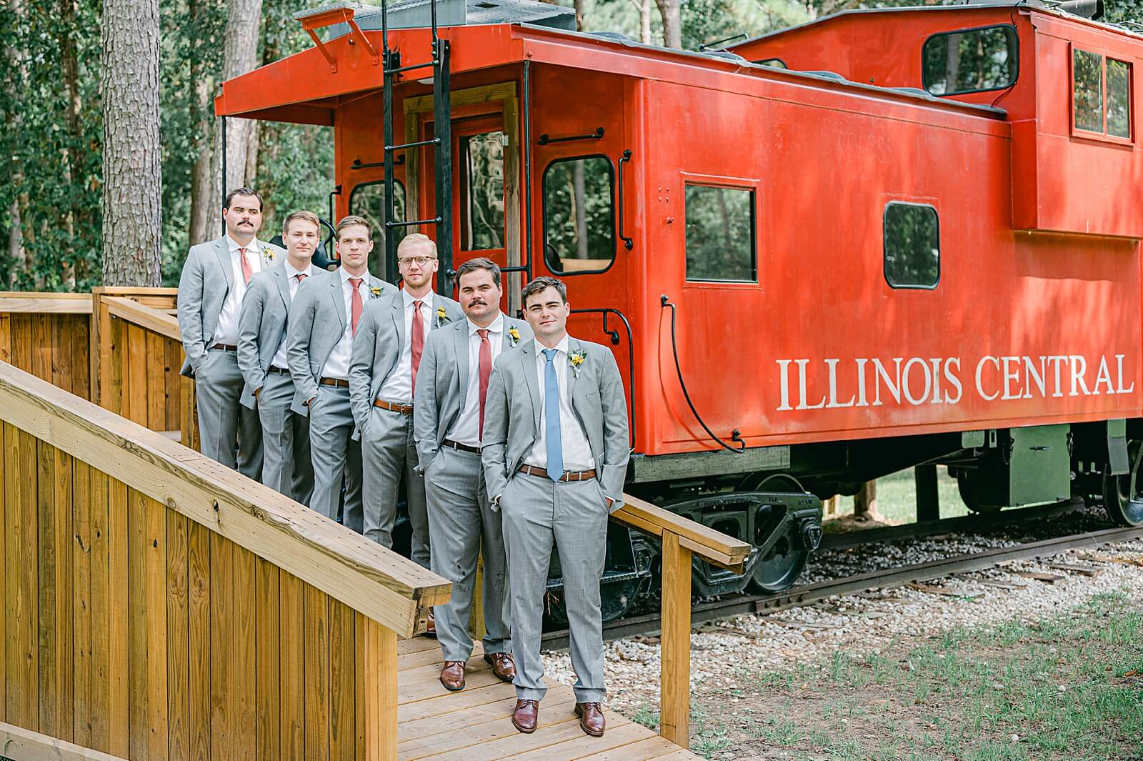 Groomsmen in front of caboose at one of the unique wedding venues in Houston The Annex