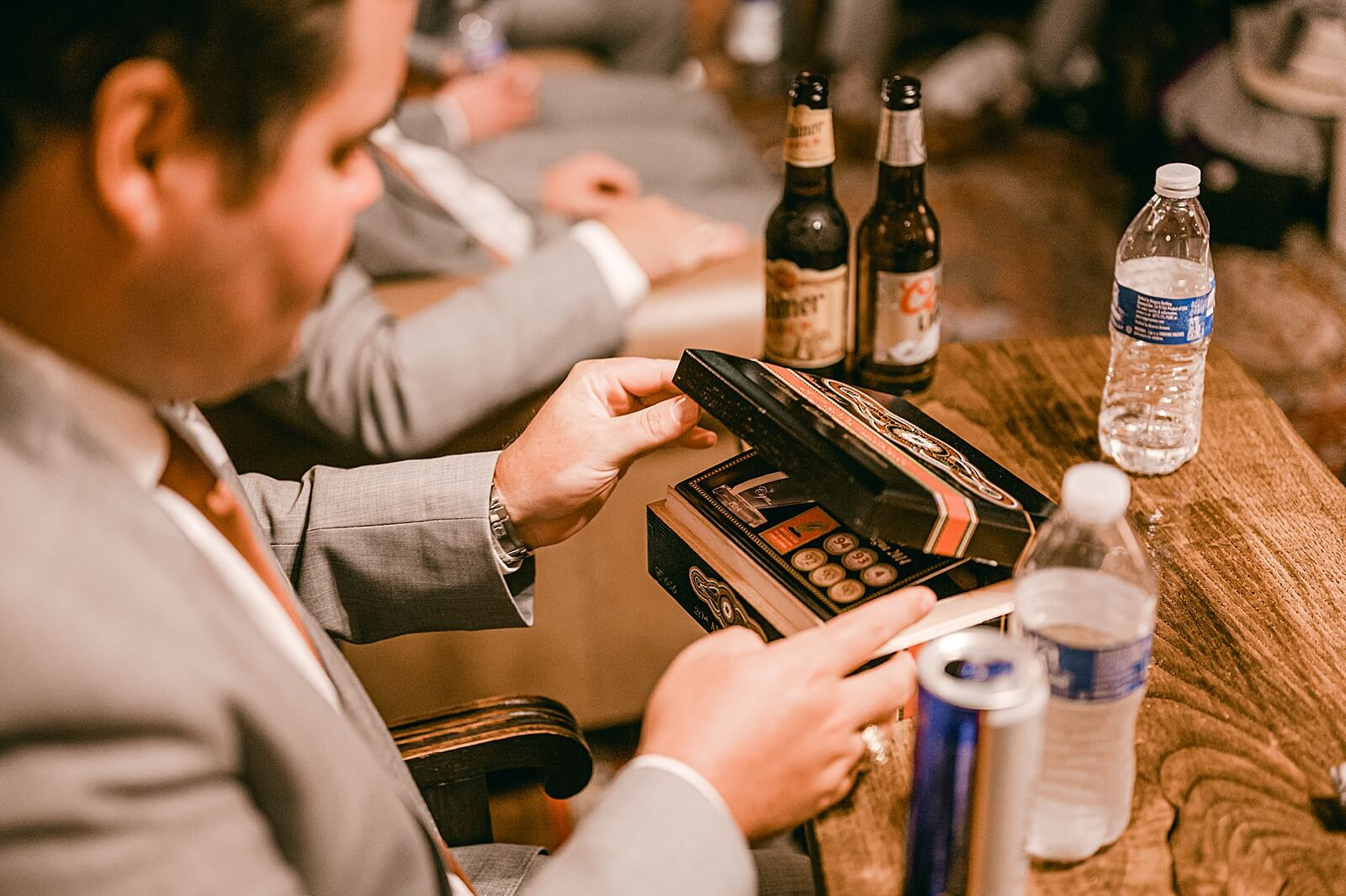 Groom opens cigar box in groom's room at one of the unique wedding venues in Houston The Annex