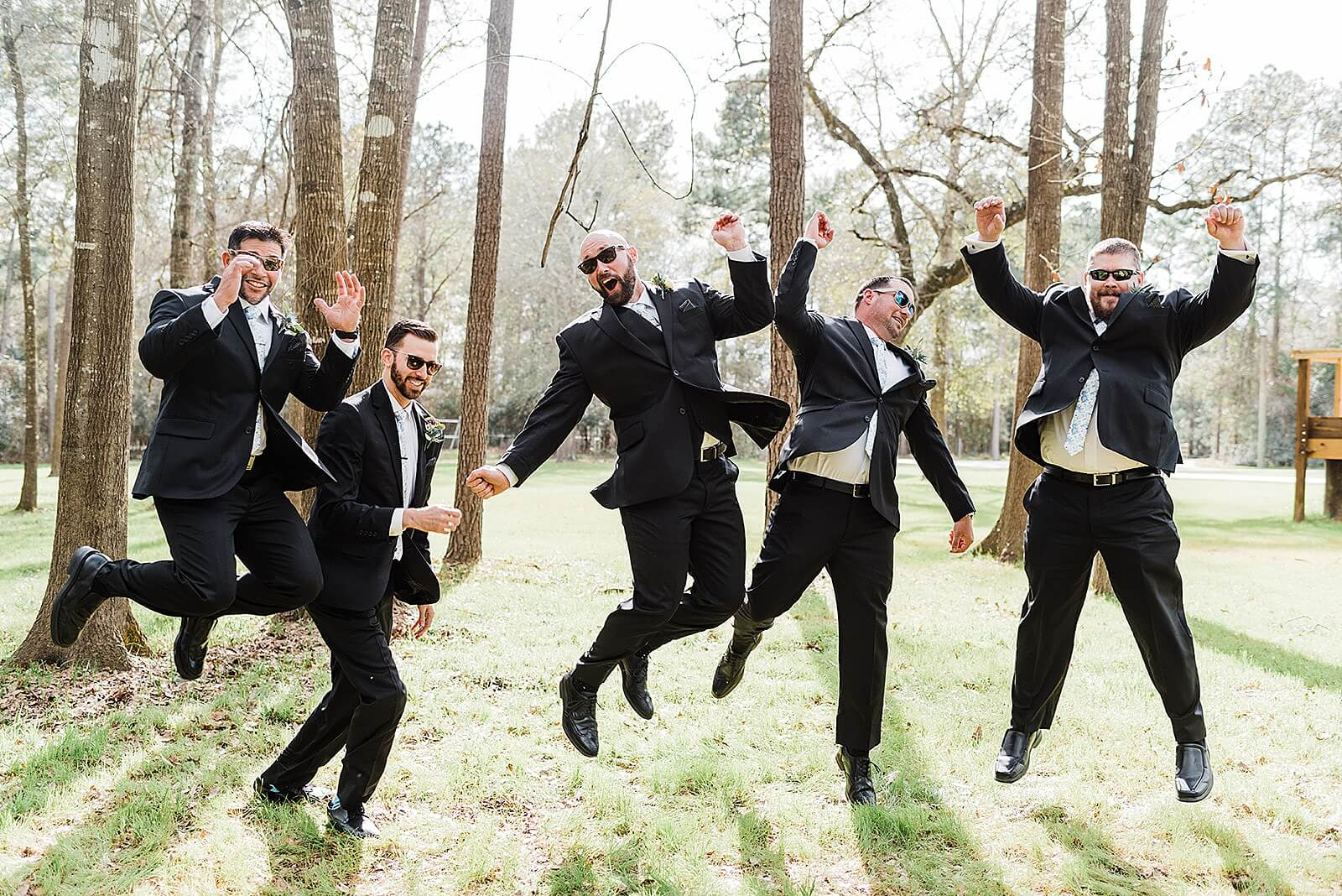 Excited groom and groomsmen jump in air at one of the unique wedding venues in Houston The Annex