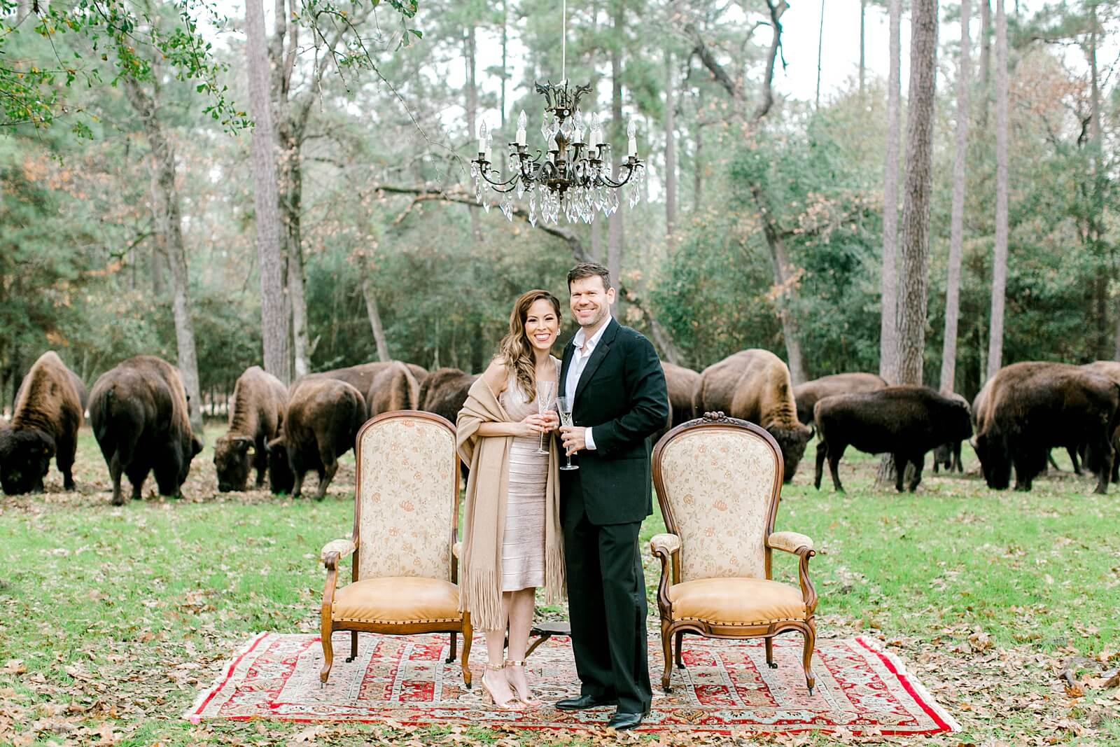 Happy couple stands under chandelier with buffalo walking behind at The Annex wedding venue