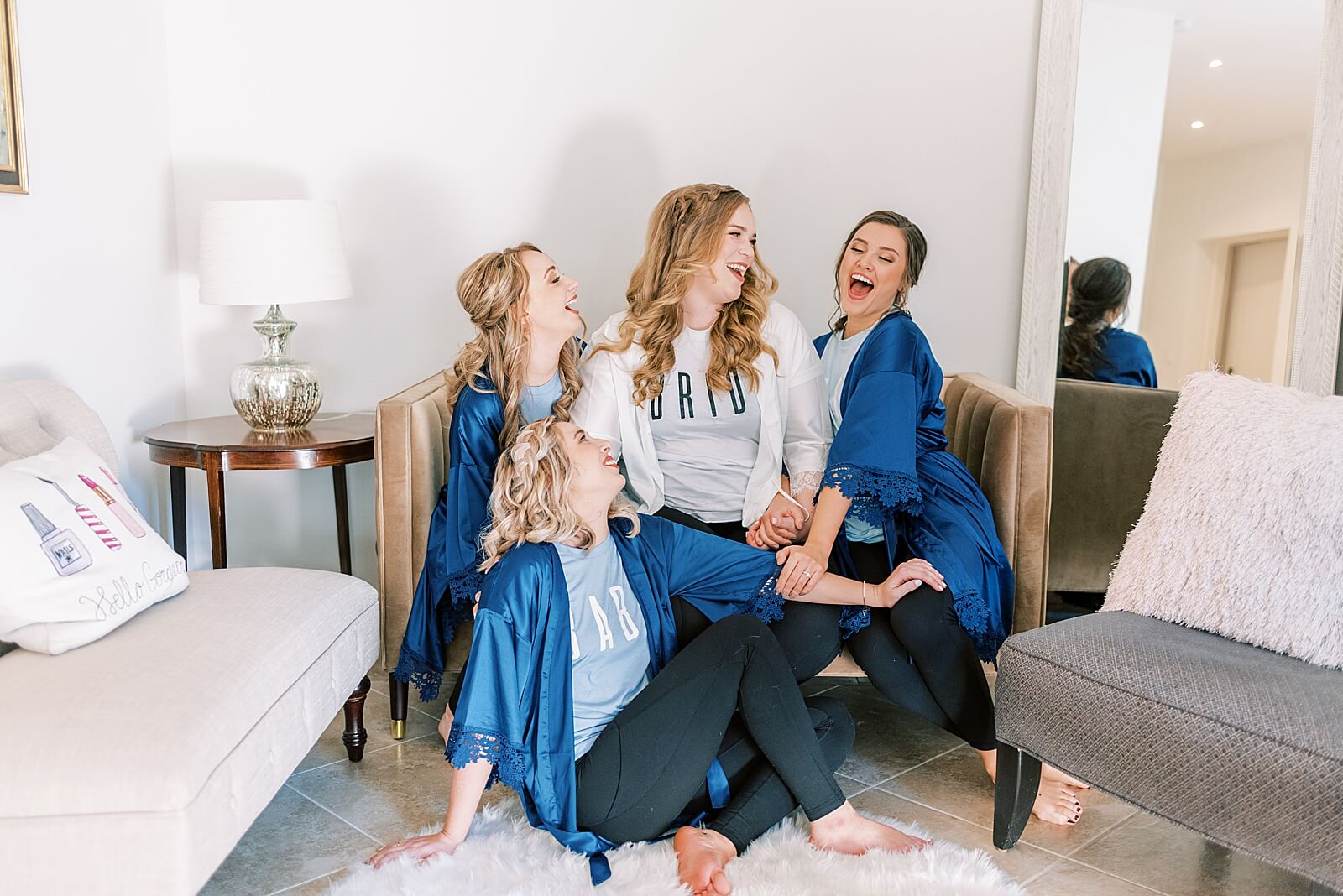 Bridal party sitting on couch laughing in one of the best bridal suites in Houston The Annex