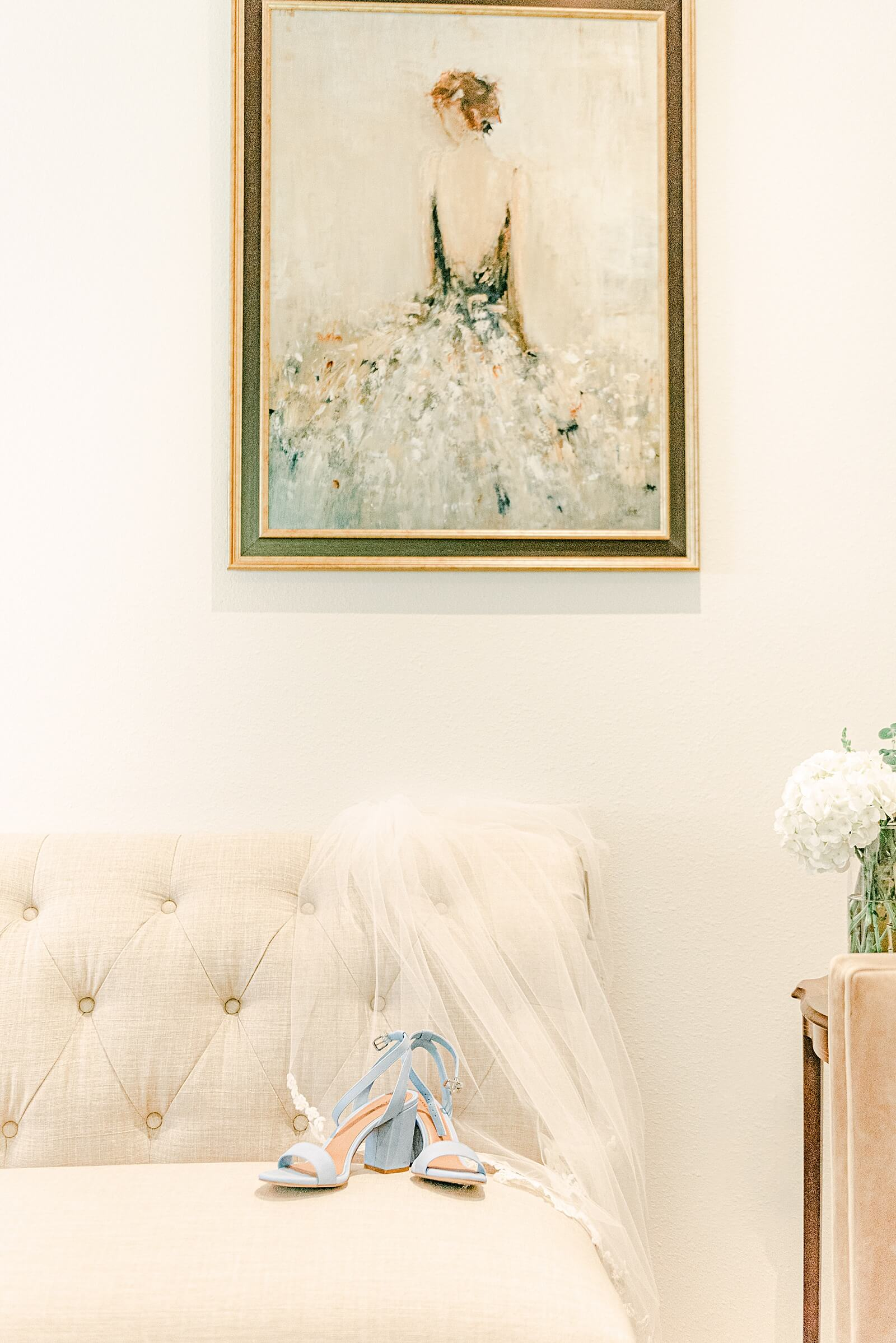 Bridal veil and shoes lay beautifully across loveseat in bridal suite at The Annex wedding venue near College Station
