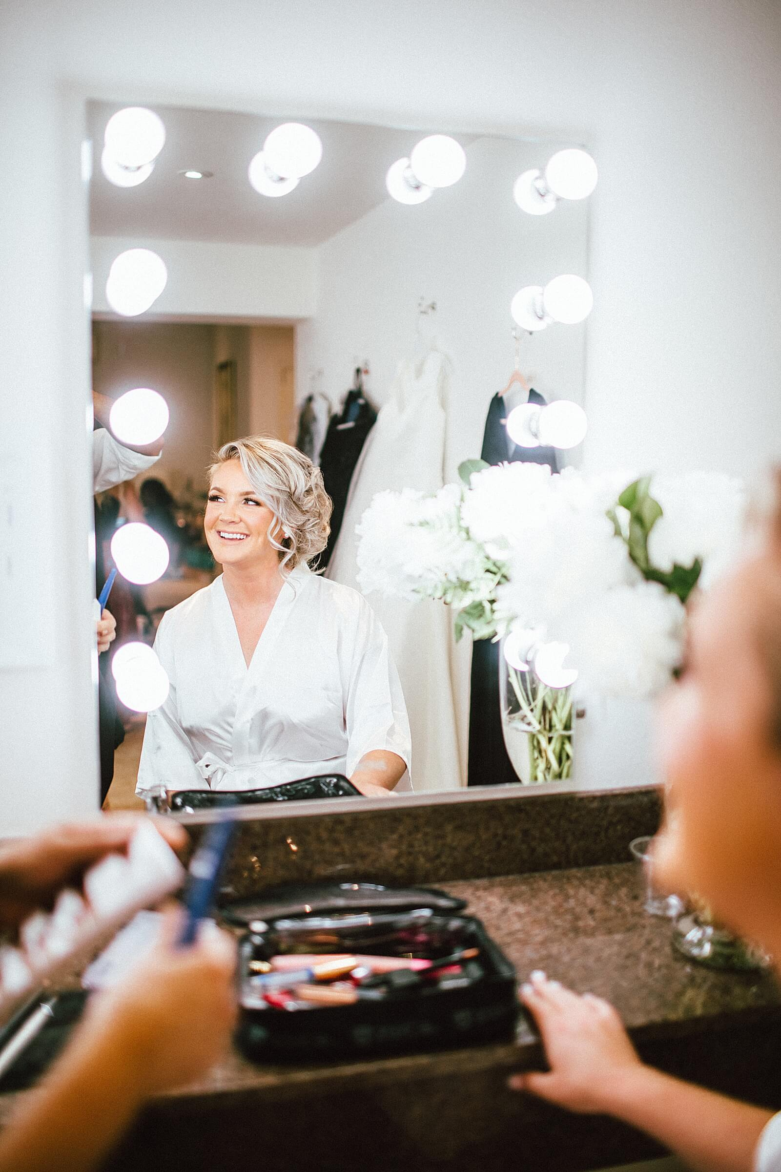 Bride looks in mirror and admires her bridal makeup in bridal suite at The Annex wedding venue near College Station