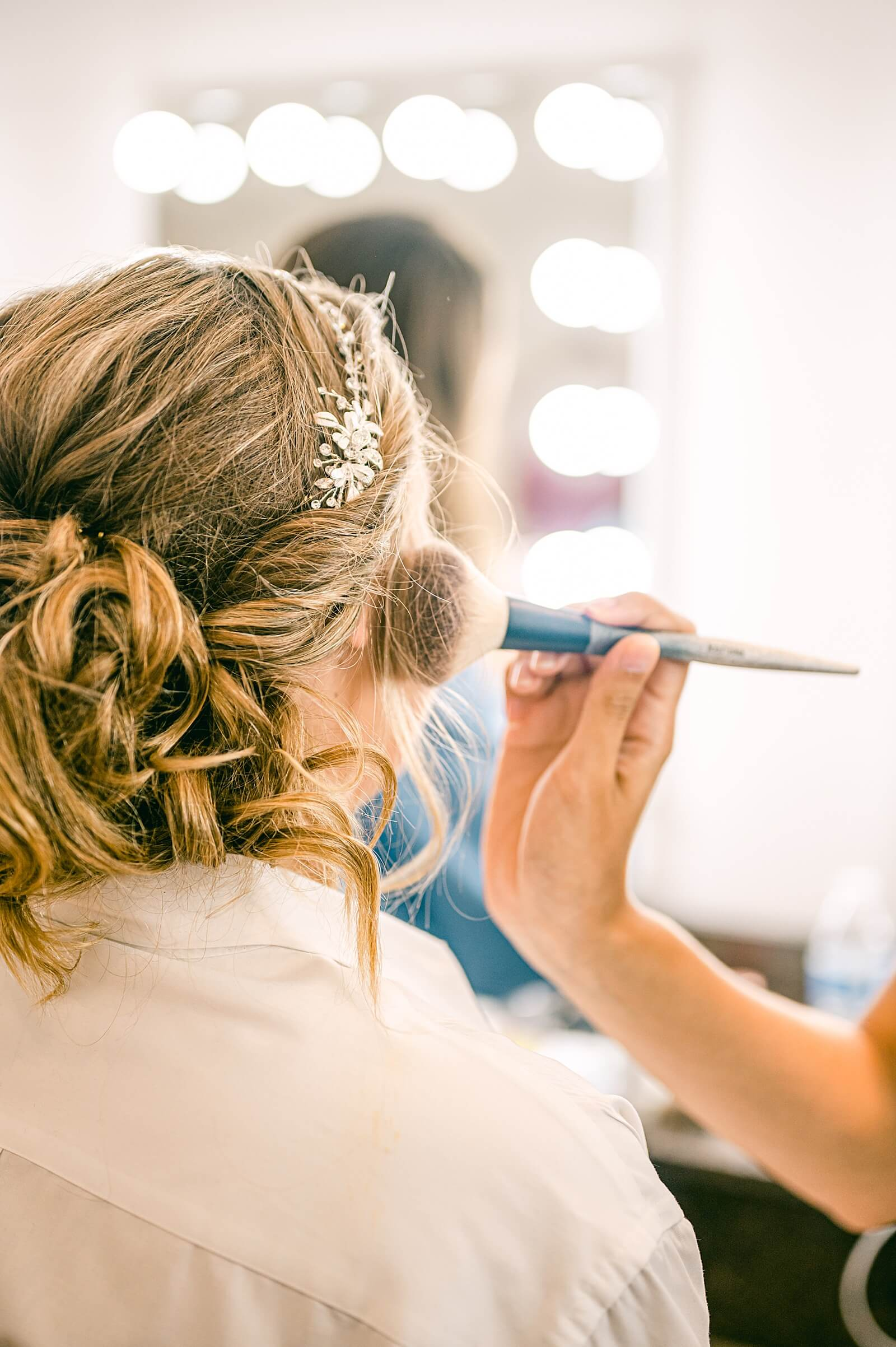 Bride putting on makeup in one of the best bridal suites in Houston The Annex