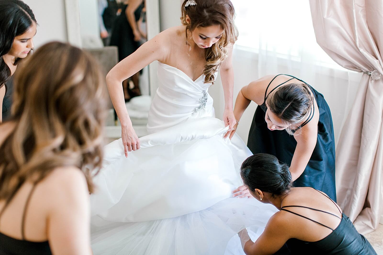 Bridesmaids help bride put on shoes before wedding at The Annex wedding venue near College Station