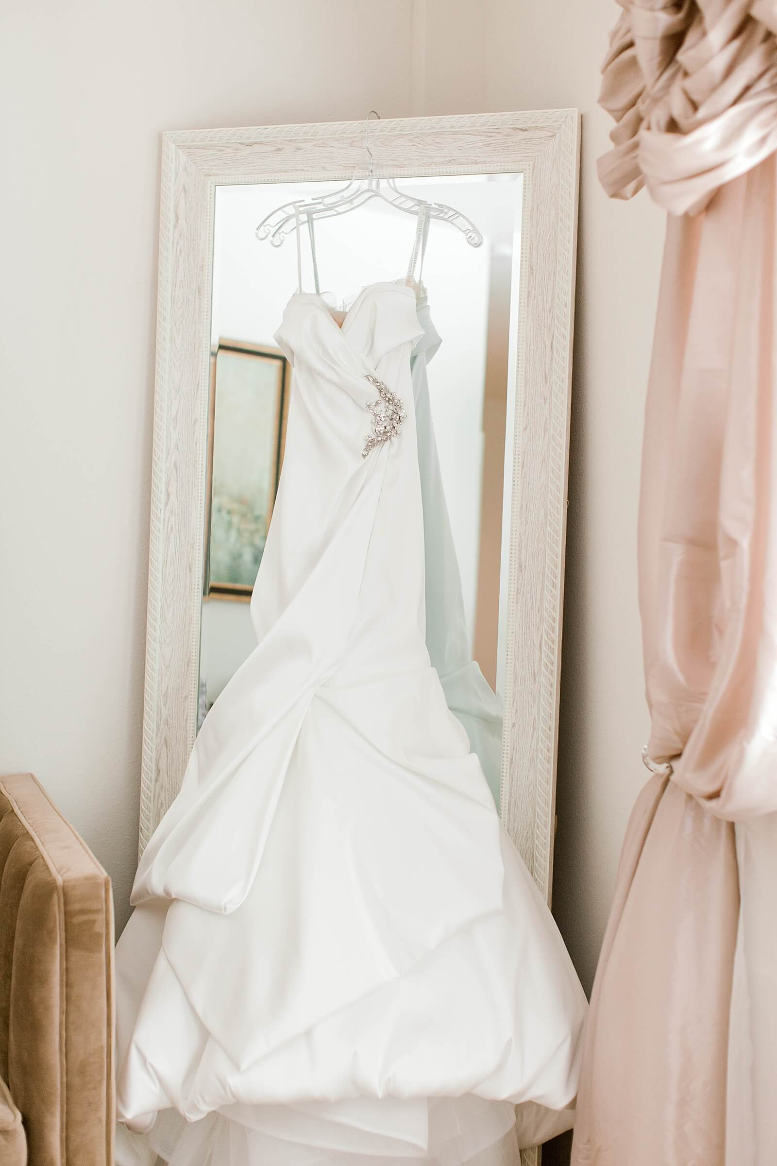 Classic wedding dress hanging on mirror in bridal suite at The Annex wedding venue near College Station