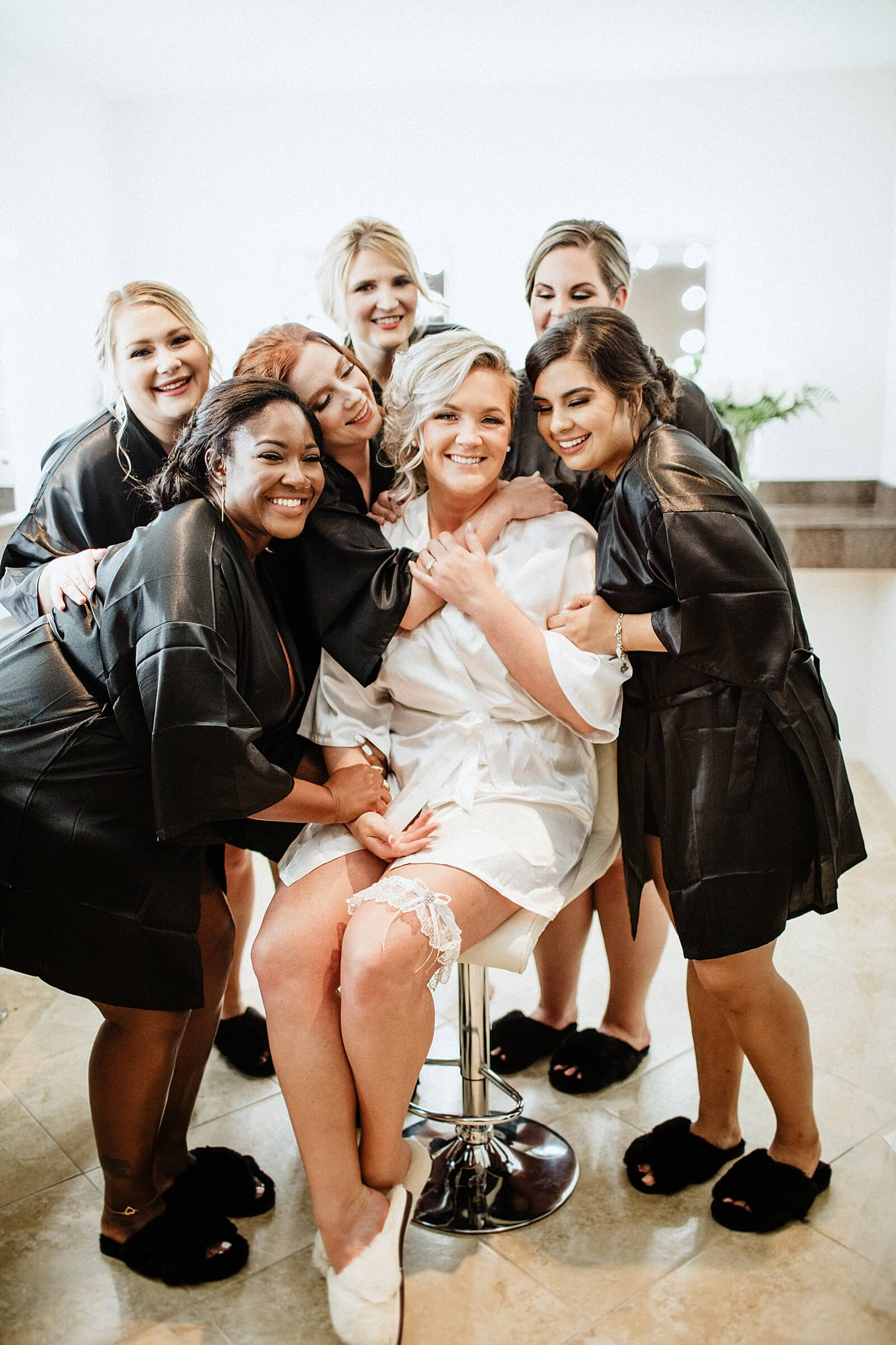 Happy bride surrounded by bridesmaids in one of the best bridal suites in Houston The Annex